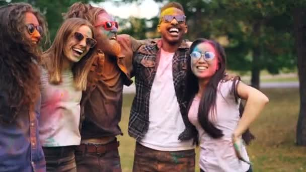 Slow motion of happy playful people jumping together holding each others shoulders laughing and having fun with colorful faces and clothing. Friendship and fun concept.