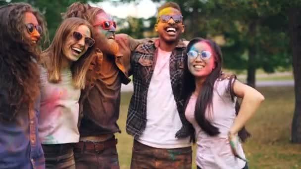 Zpomalený pohyb šťastných hravé lidí skákání, pohromadě drží navzájem ramena směje a baví s barevnými plochami a oblečení. Přátelství a zábava koncept