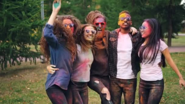 Slow motion portrait of excited young women and men in dirty clothing jumping together on lawn in park with colorful faces and hands having fun at party.