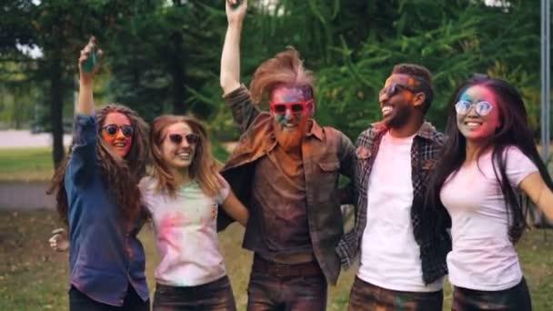 Portrét radostné mládí na Holi festival s jasně pomalované tváře a vlasy skákání, pohromadě drží navzájem ramena vyjadřují pozitivní emoce.