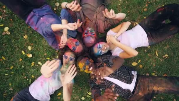 Joyful girls and guys are lying on grass in park, their faces and clothing are covered with bright multicolor paint, people are moving hands and smiling looking at camera.