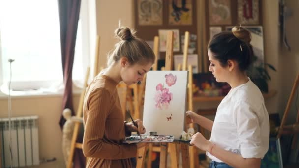 Beautiful blond girl is depicting flowers at art class under guidance of experienced teacher standing together near easel. Painting tools and artworks are visible.