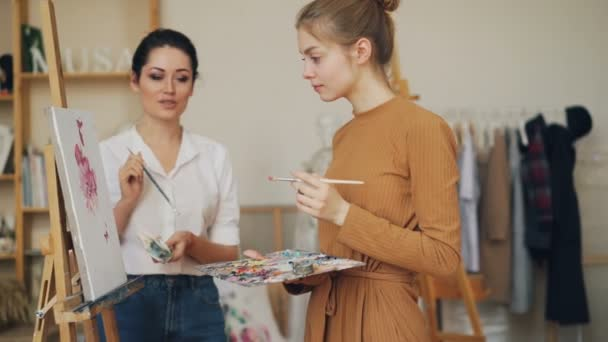 Beautiful girl art student is talking to her teacher looking at picture on easel and holding brush and palette, master is giving advice and sharing knowledge.