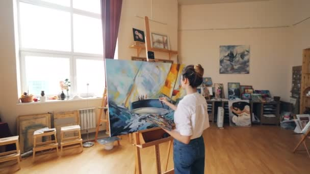 Pretty Blond Girl Artist Is Painting Marine Landscape Working In Light Workshop Alone Using Brush And Palette Tools And Artworks On Shelves Are Visible
