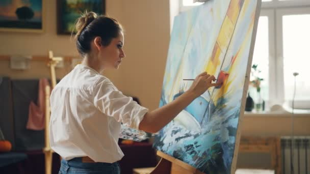 Professional artist young woman is painting seascape with acrylic paints finishing marine landscape ship and sea waves working alone in cozy studio. People and work concept.