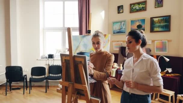 Experienced artist is teaching cute girl student to paint flowers explaining her painting technique and sharing knowledge and experience. Artistry and education concept.