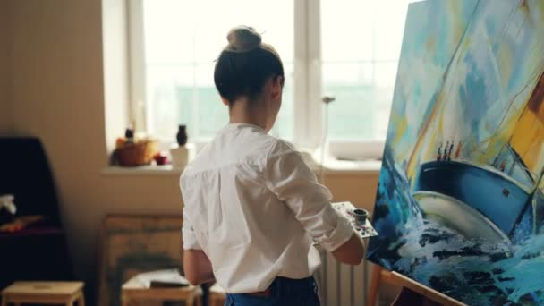 Professional female painter is working at picture using oil paints and  palette-knife creating beautiful seascape on canvas  Painting technique and  tools concept
