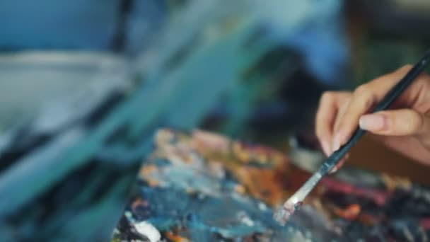 Close-up shot of female hand with paintbrush mixing colors in palette then painting beautiful picture creating masterpiece. Artistic work and youth concept.