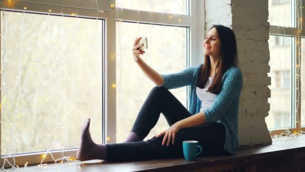 Girl is talking with friends online making video call with smartphone talking and laughing sitting on window-sill enjoying communication. Technology and conversation concept.