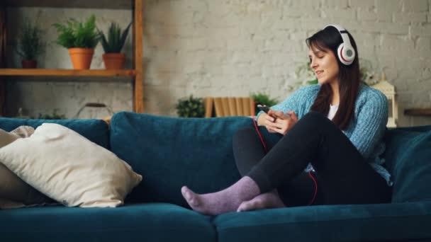 Radostné mladá dáma je poslech hudby do sluchátek, pomocí smartphone, usmívá a směje se, sedí na pohovce v domácí, užívat si odpočinku a pohodlí
