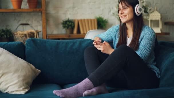 Nyugodt nő hallgat zenét vezeték nélküli haedphones, használ smartphone képernyő megérintésével, és élvezi a többi otthon a kanapén. Szórakoztató és modulok koncepció.