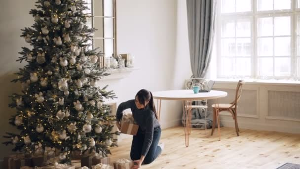 Attractive girl is bringing gift boxes to Christmas tree, putting them under fir-tree and smiling then touching beautiful decorations. Holidays and presents concept.