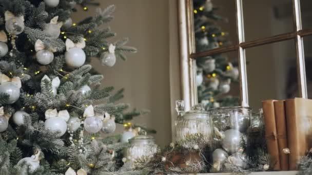 Közeli lövés tökéletes karácsonyi dekoráció kandalló kiegészítők és zöld új év tree ezüst golyó és a fények ágai. Boldog karácsonyt-koncepció