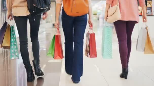 Alacsony lövés, a séta a bevásárló központ együtt gazdaság ajándék táska vásárlás élvezi eladó női vásárlók. Emberek, a fogyasztás és a shopaholism fogalma.