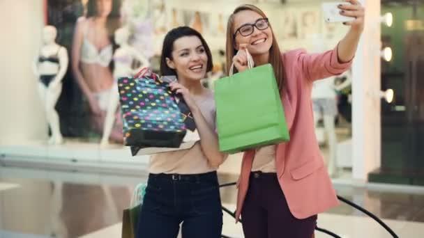 Happy shopaholics berou selfie s papírové tašky do nákupního centra pomocí smartphone fotoaparát zařízení a pózování, smáli se a baví. Koncepce životního stylu mládeže.