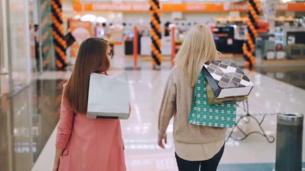 Pomalý pohyb veselá mladé dámy spokojených zákazníků chůzi společně v nákupní centrum drží barevné papírové tašky pak obrací na kameru a usmívá se. Koncept Shopaholics a obchody