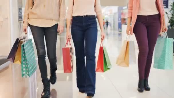 Nízká rána nohám dámy v nákupním centru s papírové sáčky těší nákup oblečení a dárky. Životní styl, přátelství a konzumu koncepce mládeže.