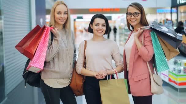 Portrét dobře vypadající dívky nosí módní oblečení a doplňky drží nákupní tašky ve velké nákupní centrum při pohledu na fotoaparát a usmívá se. Koncept lidé a obchody