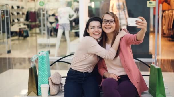 Good-looking young ladies are taking selfie together using smartphone sitting in shopping mall resting and having fun. Girls are hugging and posing with hand gestures.