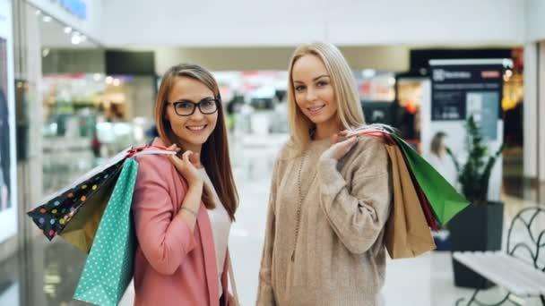 Portrét krásné dívky drží nákupní tašky ve velkém obchodě při pohledu na fotoaparát a usmívá se. Mladé ženy nosí módní oděvy a doplňky