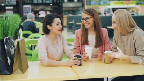 Good-looking girls are toasting and clinking glasses with drinks sitting in cafe in shopping mall then chatting and laughing having fun together. Friendship and leisure concept.