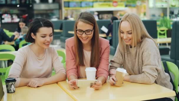 Radostné mladé dámy používáte smartphone společně při pohledu na obrazovku usmívá a směje posezení v útulné kavárně v nákupní centrum s papírem tašek viditelné. Gadgets a zábavné pojetí.