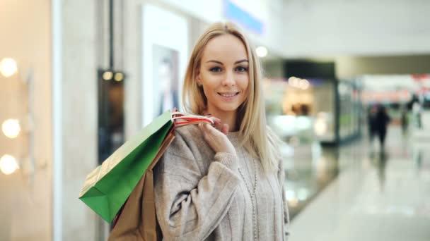 Portrét krásnou slečnu s dlouhé blond vlasy, při pohledu na fotoaparát a usmívá se postavení v nákupní centrum s papírové sáčky. Moder mládež a nákupní věci koncept