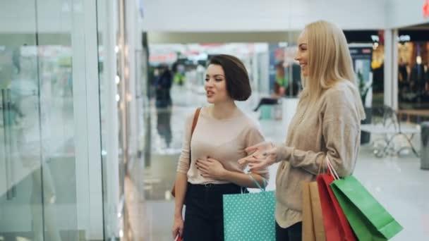 Dívky jsou chatování v nákupní centrum diskuse o nové kolekci spodního prádla na oblečení na panáky a nehýbej se. Koncept prodeje, zákazníky a lidé.
