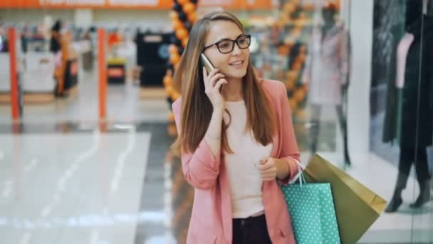 Good-looking young lady is talking on mobile phone walking in shopping mall alone carrying paper bags. New clothing on dummies behind glass walls is visible.