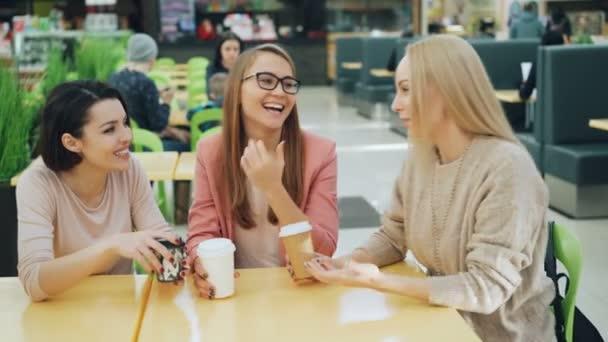 Giovani felici sono parlando e ridendo in caffetteria quindi che clinking i vetri celebrando reunion che si siedono insieme al tavolo e godere di buona compagnia. Bevande e divertimento concetto