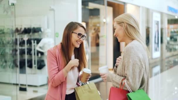 Meg Aranyos lányok beszélgetni, és nevetett eltávolítás italok és színes papír táskák, bevásárló központ. Vidám beszélgetés, jó hangulat és ifjúsági koncepciót.