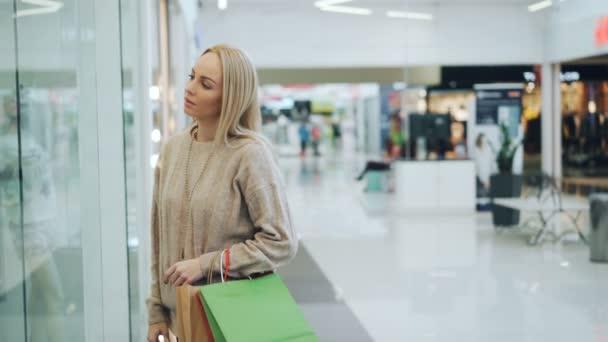 Šťastné mladé ženy se sejdou v nákupní centrum diskuse o nákupy a při pohledu na zboží v papírových taškách pak bude nakupovat společně. Přátelství a shopaholics koncept.