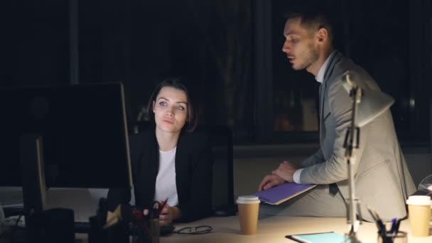 Serious businesspeople man and woman in suits are working together in dark office late at night looking at pc screen and talking discussing job issues.