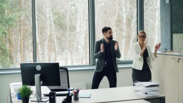 Good-looking young people coworkers are dancing in office and clapping hands enjoying music and relaxation. Youth lifestyle, job and partying concept.