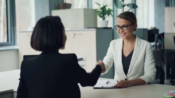 Good-looking young lady from human resources department is interviewing a female professional shaking hands then asking questions and writing. Employment and youth concept.