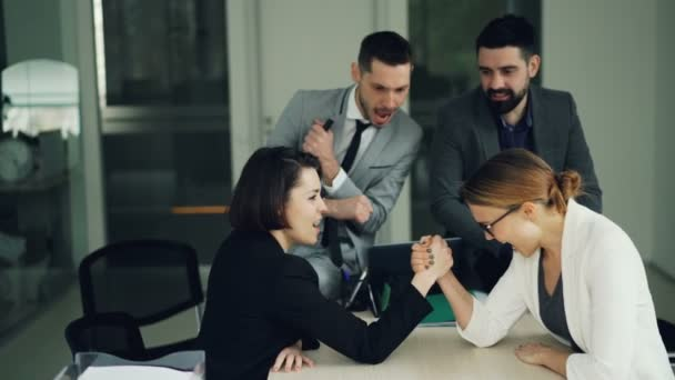 Funny girls coworkers are having fun with arm wrestling at table in office while colleagues are watching then laughing, clapping hands and doing high-five.