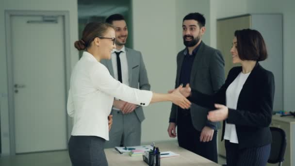 Company CEO is congratulating a successful candidate after job interview, shaking her hand and smiling, people are clapping hands and expressing positive emotions.
