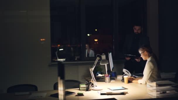 Manažer společnosti mluví s jeho zaměstnanec pracující v noci dávat rozkazy a diskutovat o práci s počítačem. Lidé jsou na sobě formální obleky