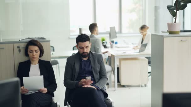Stressed candidates are waiting for job interview in office reading cv and using smartphone while female manager is interviewing a man in room. Company and staff concept.