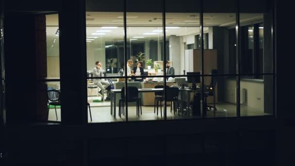 Skupina lidí obchodního týmu pracují v kanceláři pozdě v noci na mobilním telefonu, diskutovat o práci a při pohledu na dokumenty. Pohled z venku z panoramatické okno