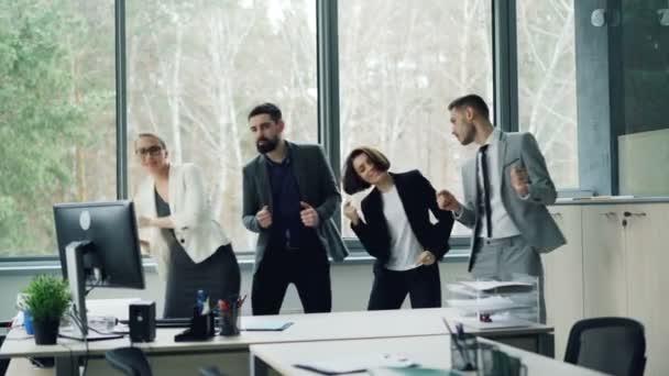Happy bezstarostné spolupracovníky z tancuje v kanceláři slaví firemní akci, večírku, směje se a baví. Koncept mládeže, práce a emoce.