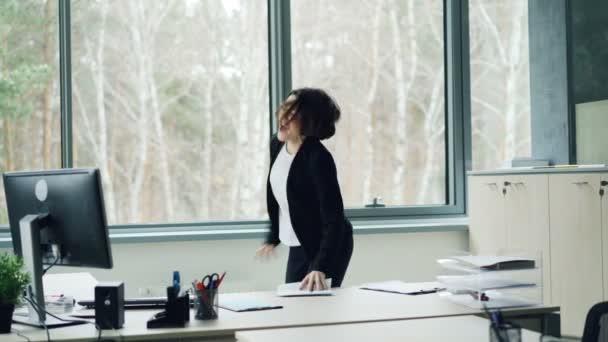 Radostné podnikatelka slaví firemní akce radosti nad dobrou zprávou křičí, hází kancelářské papíry a sundala kabát tančit a skákat