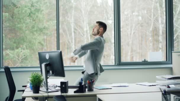 Dobře vypadající vousatý muž v obleku tancuje v místnosti úřadu sám, pohybující se tělo a paže a pak brát papíry od stolu a házet je na podlaze. Koncept radosti a emocí.
