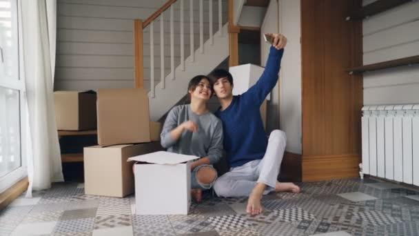 Šťastná rodina manžela a manželky berou selfie s klíče od domu sedí na podlaze nového bytu poblíž lepenkových krabic s věcmi. Přemístění a koncepce sociálních médií.