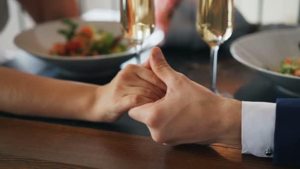 Nahaufnahme von zwei Händen Mann und Frau auf einem Tisch mit prickelnden Champagnergläsern und Tellern mit Essen. Romantik, junge Liebe und Restaurantkonzept.