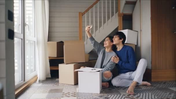 glückliches Paar macht Selfie nach dem Kauf einer neuen Wohnung. Junge Leute posieren und küssen und schauen in die Smartphone-Kamera mit Kästen im Hintergrund.
