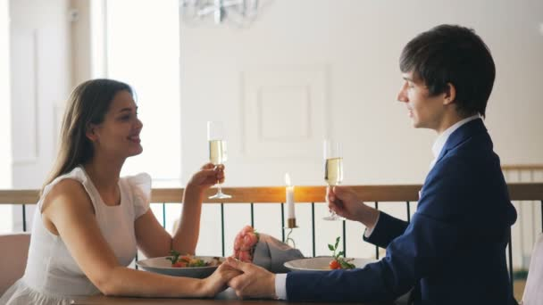 Loving young man is talking to his fiancee holding champagne glass then clinking glasses and drinking during romantic date in restaurant. Youth and dating concept.