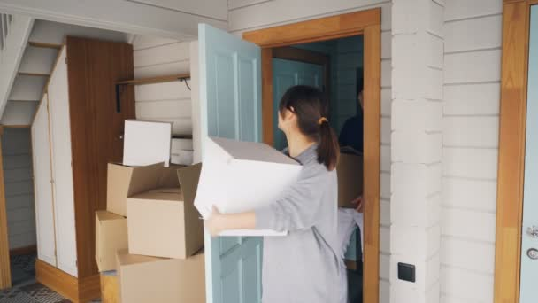 Man and woman with carton boxes are opening door, entering their new house, looking around and kissing then going upstairs carrying things. Relocation and family concept.