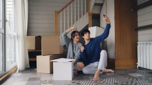 Die hübsche junge Frau und ihr Mann telefonieren während des Umzugs online mit dem Smartphone. Menschen zeigen neue Hausschlüssel und Schachteln, reden und lächeln.