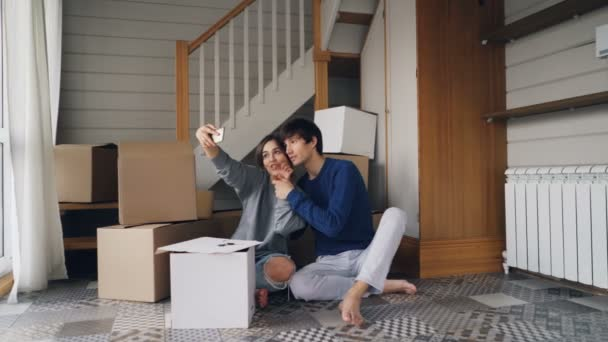 Young man and woman are taking selfie with smartphone making heart shape with fingers sitting on floor of new apartment with boxes in background. Relocation and fun concept.